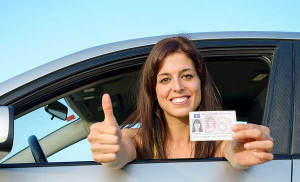 Водитель держит в руке водительское удостоверение