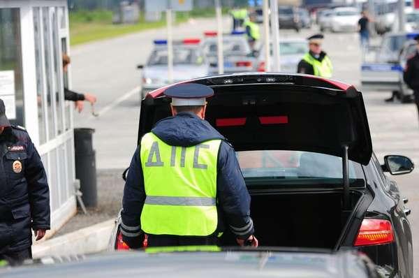 Сотрудник ДПС производит осмотр багажника автомобиля