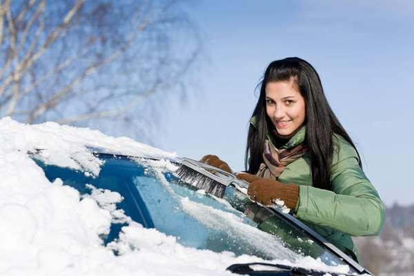 Девушка чистит машину от снега